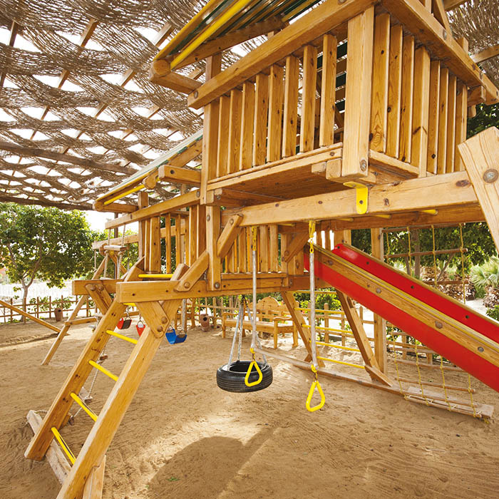 Childrens wooden climbing frame with slide in a playground at park